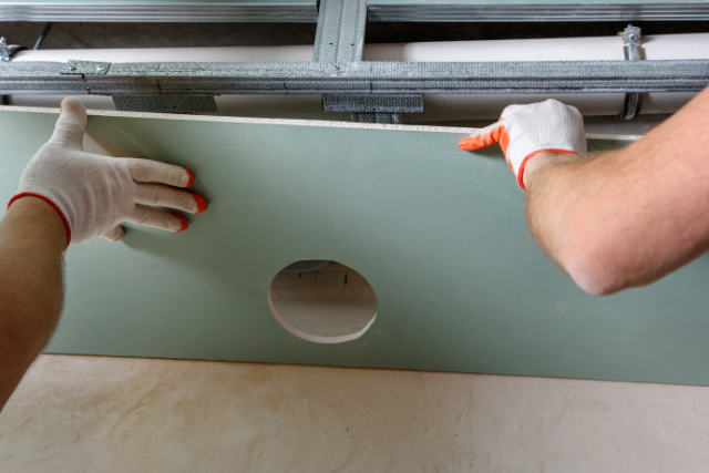 Drywall Installation by two workers with gloves on