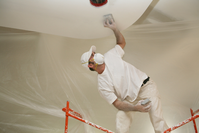 Portland Drywall Sanding by a worker on a scaffold and mask on.