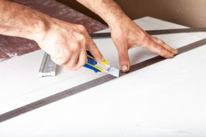 Portland Drywall repair by worker with a knife and a ruler